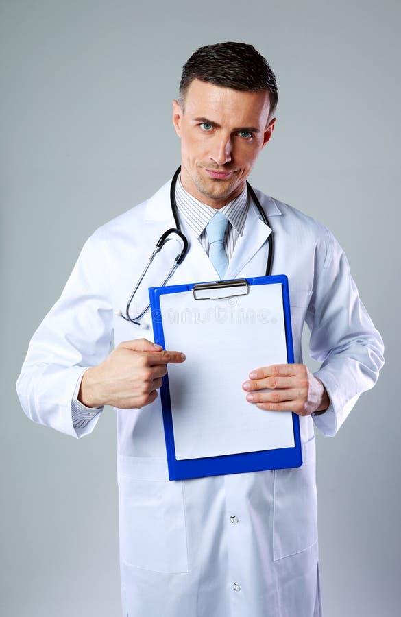 Docteur masculin montrant sur le presse-papiers vide photos libres de droits