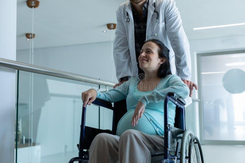 Docteur masculin poussant la femme enceinte sur le fauteuil roulant dans le couloir photographie stock libre de droits