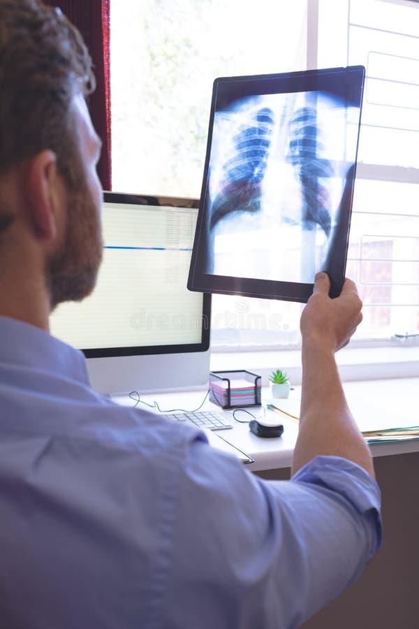 Docteur masculin regardant le rayon de x dans la clinique photographie stock