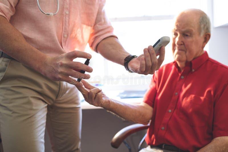 Docteur masculin sûr examinant le patient d'homme supérieur avec le glucometer photos libres de droits