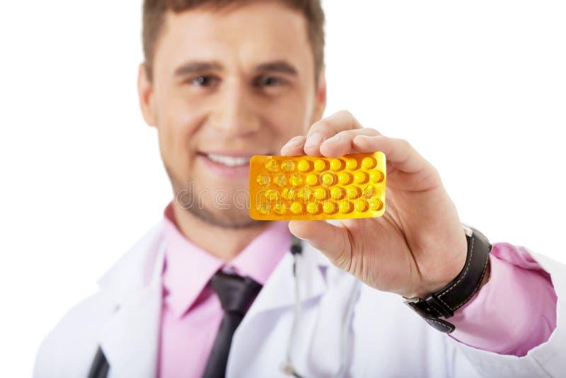 Docteur masculin tenant des pilules photos stock