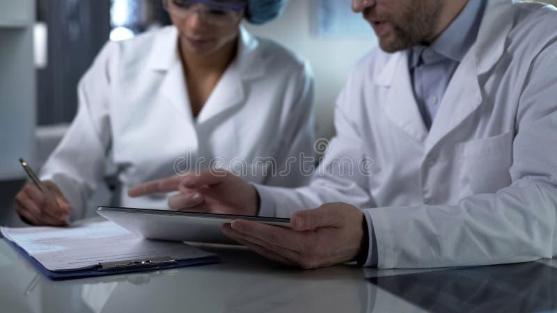 Docteur masculin tenant le comprimé, donnant des instructions auxiliaires femelles de noter vers le bas images stock