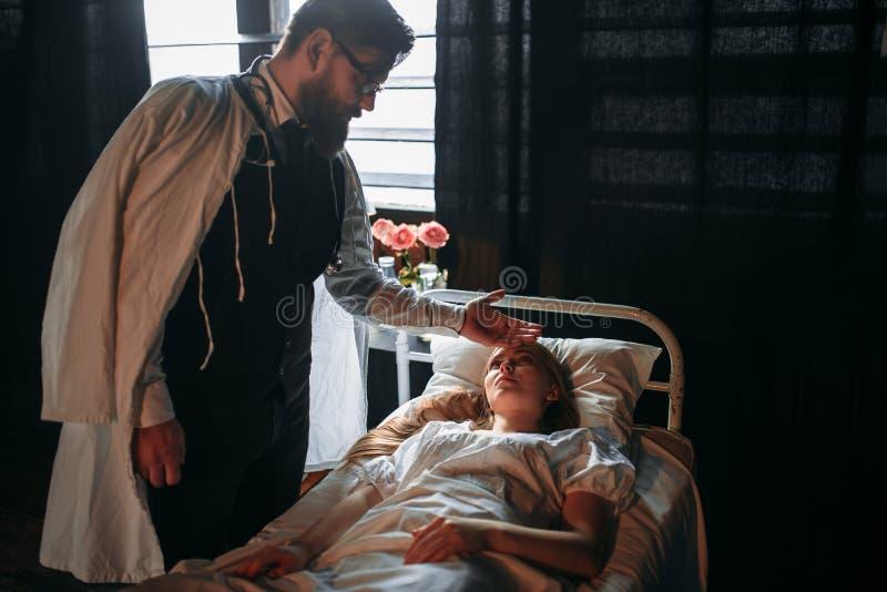 Docteur masculin touchant le front de la femme malade photographie stock