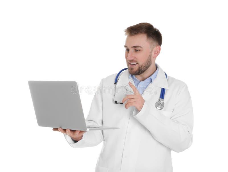 Docteur masculin utilisant la causerie visuelle sur l'ordinateur portable contre le blanc image stock