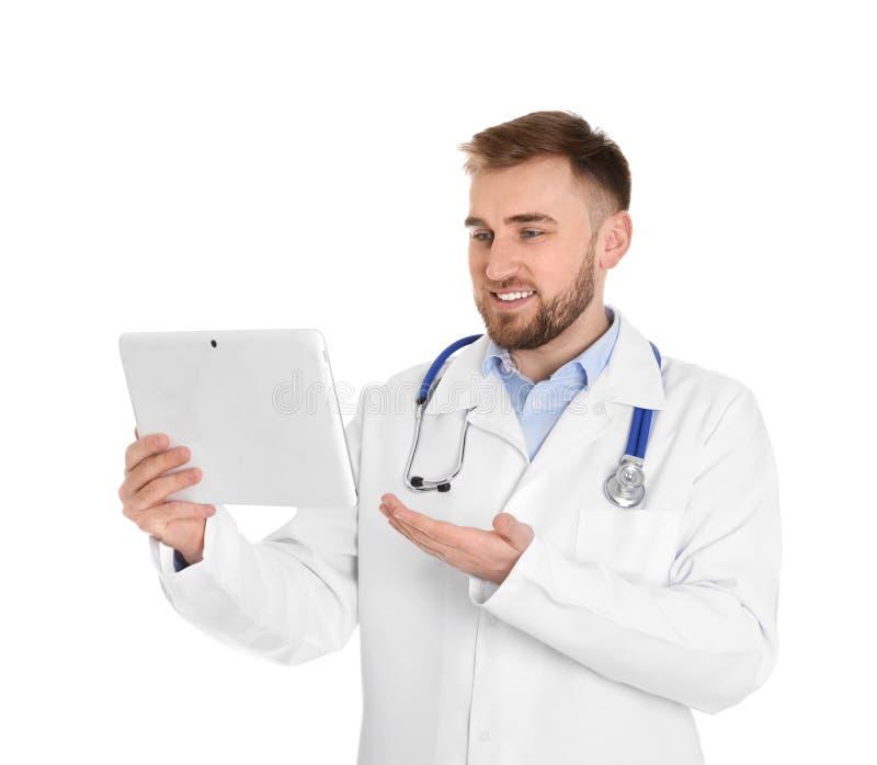 Docteur masculin utilisant la causerie visuelle sur le comprim? contre le blanc photographie stock