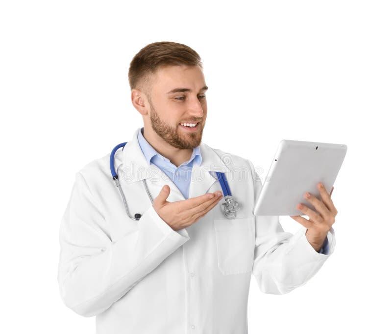 Docteur masculin utilisant la causerie visuelle sur le comprim? contre le blanc photographie stock libre de droits