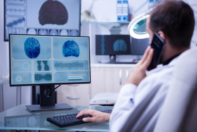 Docteur masculin utilisant le téléphone tout en travaillant à la dactylographie d'ordinateur photos stock