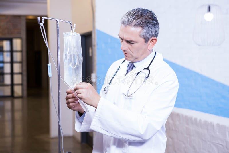 Docteur masculin vérifiant une perfusion de sérum physiologique images stock