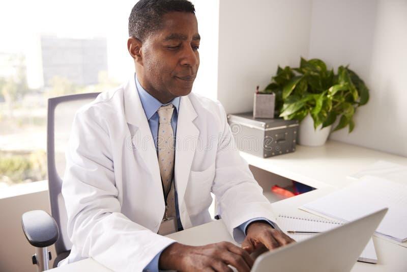 Docteur masculin Wearing White Coat dans le bureau se reposant au fonctionnement de bureau sur l'ordinateur portable images libres de droits