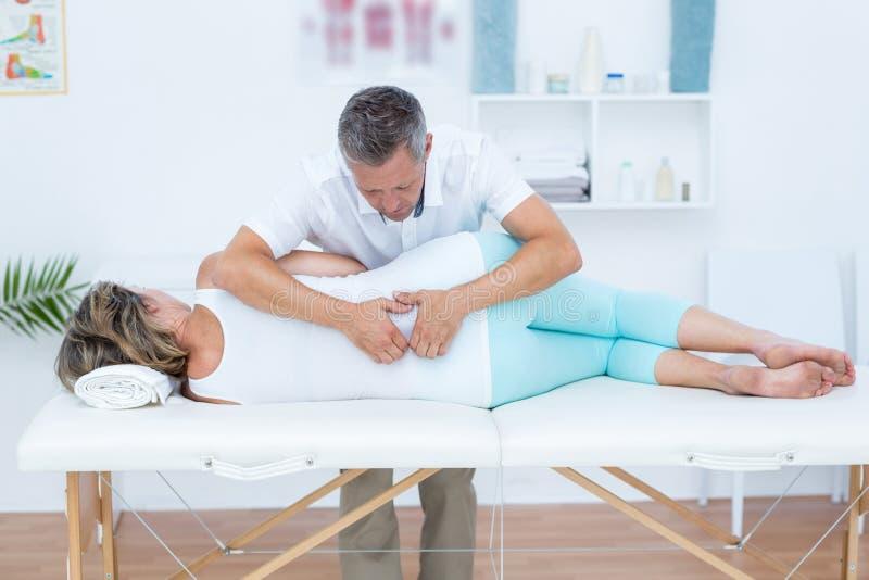 Docteur massant son dos de patient photographie stock libre de droits