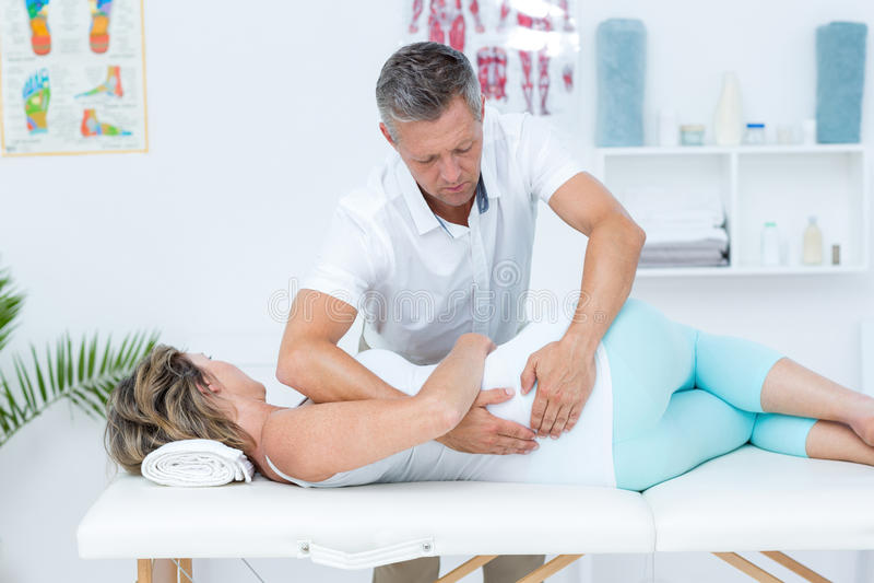 Docteur massant son dos de patient photo stock