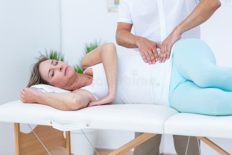 Docteur massant son estomac patient photo stock