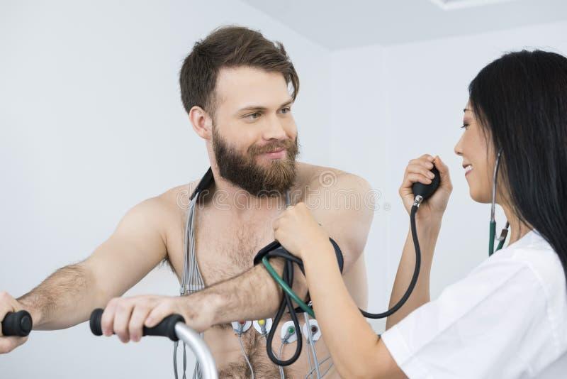 Docteur Measuring Blood Pressure de patient avec des électrodes sur la BO photo stock