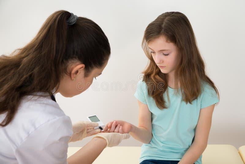 Docteur Measuring Blood Sugar Level Of Girl image libre de droits