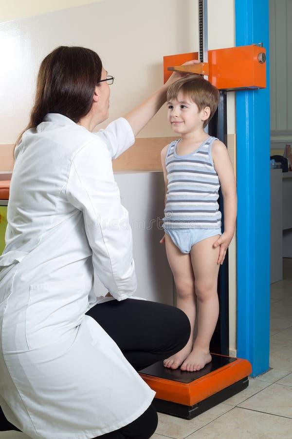 Docteur Measuring Height de Little Boy sur l'échelle médicale traditionnelle image libre de droits