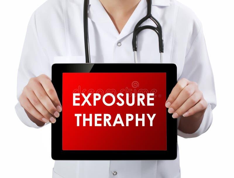 Docteur montrant le comprimé avec le texte de l'EXPOSITION THERAPHY image libre de droits