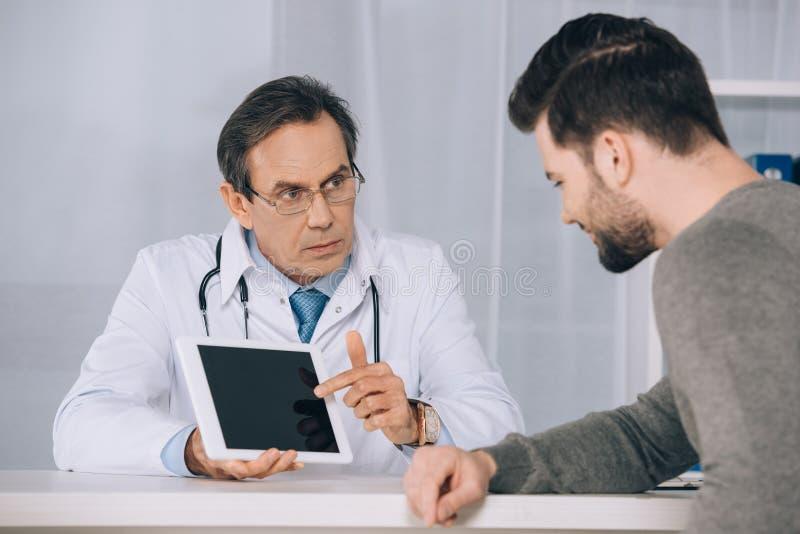 Docteur montrant quelque chose au patient photo libre de droits