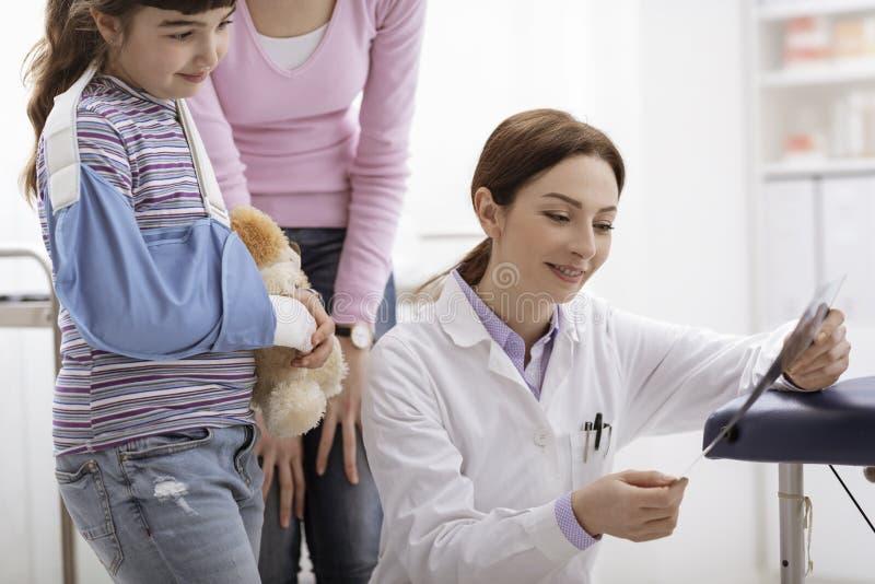 Docteur montrant un rayon X à un jeune patient avec le bras cassé photos libres de droits