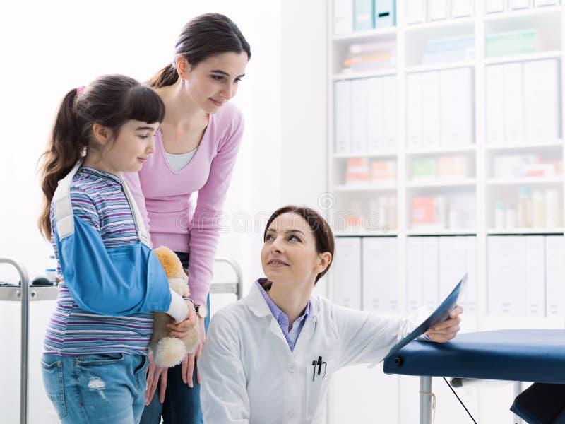 Docteur montrant une image de rayon X d'un os cassé à un jeune patient photos libres de droits