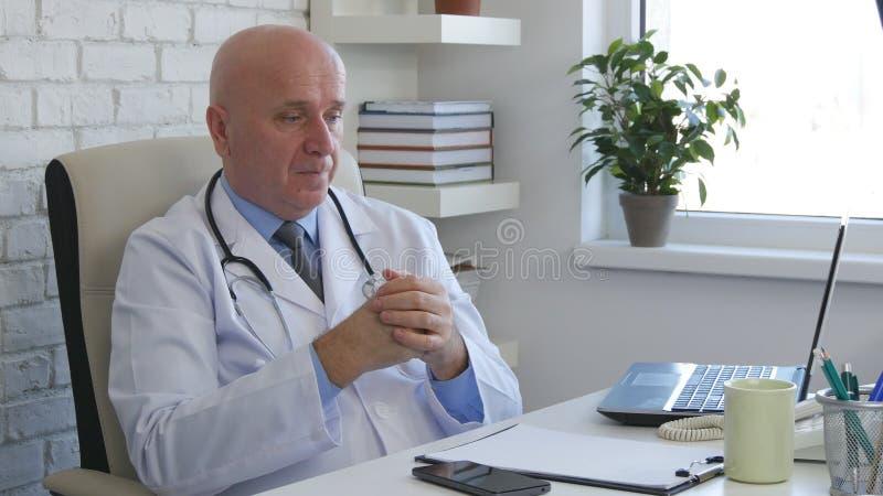 Docteur Office Job Sitting sur le bureau et la pensée photo stock