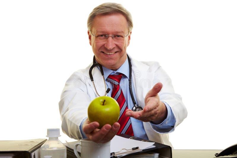 Docteur offrant une pomme photos stock