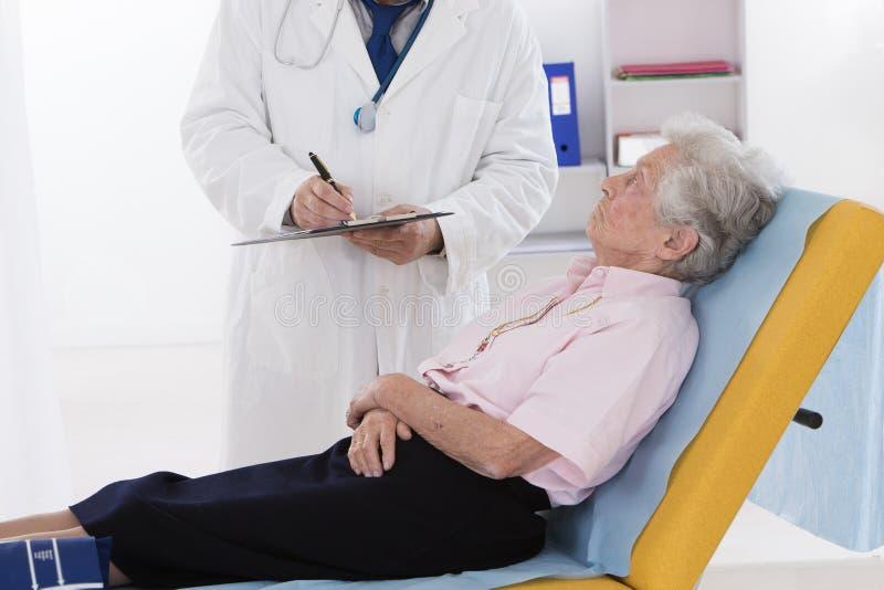 Docteur parlant à son patient supérieur handicapé photo stock