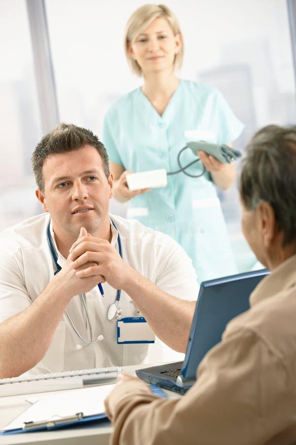 Docteur parlant au vieux patient image libre de droits
