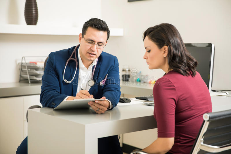 Docteur passant en revue des antécédents médicaux de patient photographie stock
