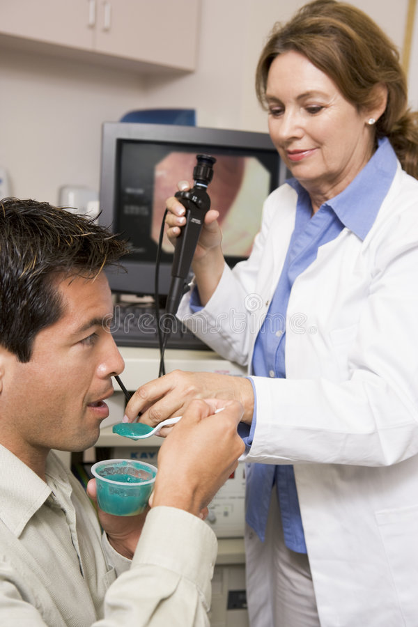 Docteur Performing Laryngoscopy On Patient images stock