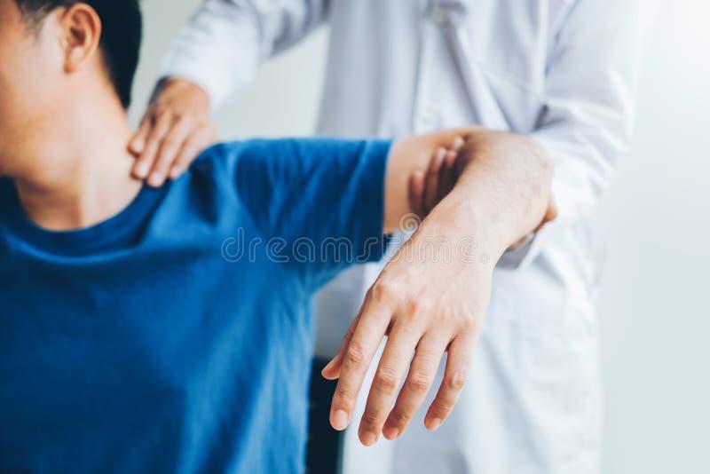 Docteur physique consultant le patient au sujet de la physiothérapie de problèmes de douleur de muscule d'épaule diagnostiquant l photo libre de droits