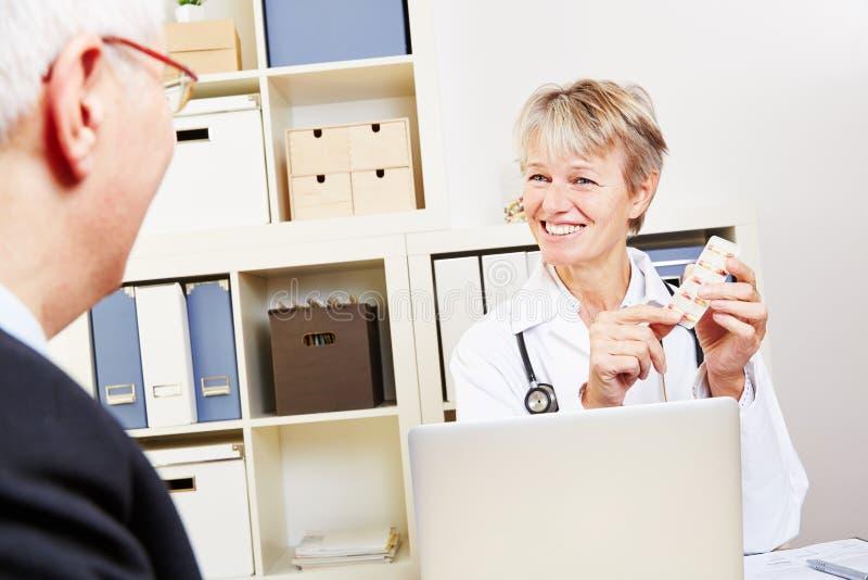 Docteur plus âgé donnant des pilules images stock