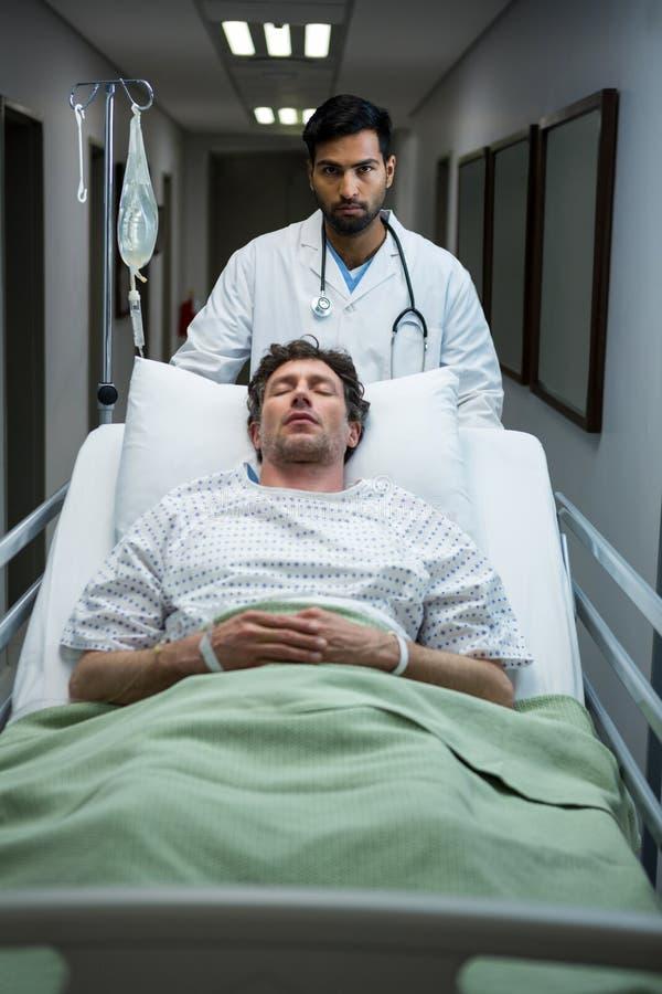 Docteur poussant le lit de civière de secours dans le couloir photo libre de droits