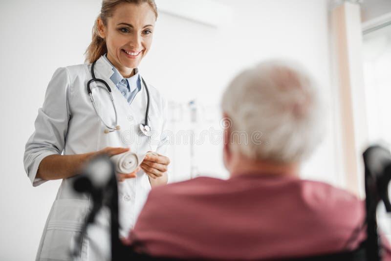 Docteur prenant soin de vieil homme dans le fauteuil roulant photo stock