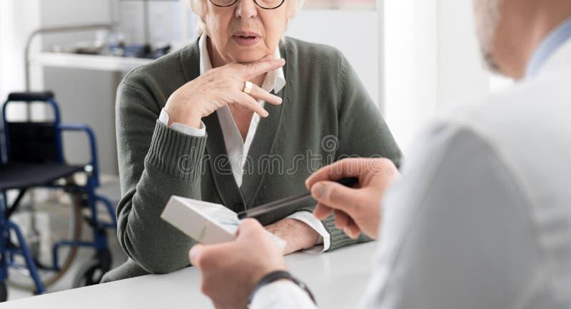 Docteur professionnel donnant une médecine de prescription à un patient supérieur photographie stock libre de droits