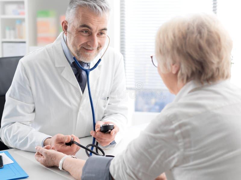 Docteur professionnel mesurant la tension artérielle d'un patient photo stock