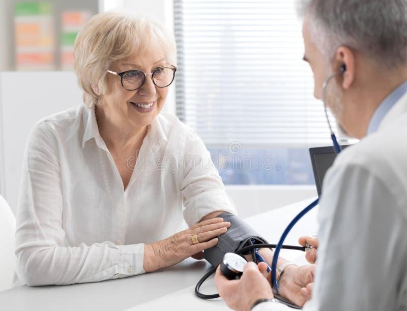 Docteur professionnel mesurant la tension artérielle d'un patient images libres de droits