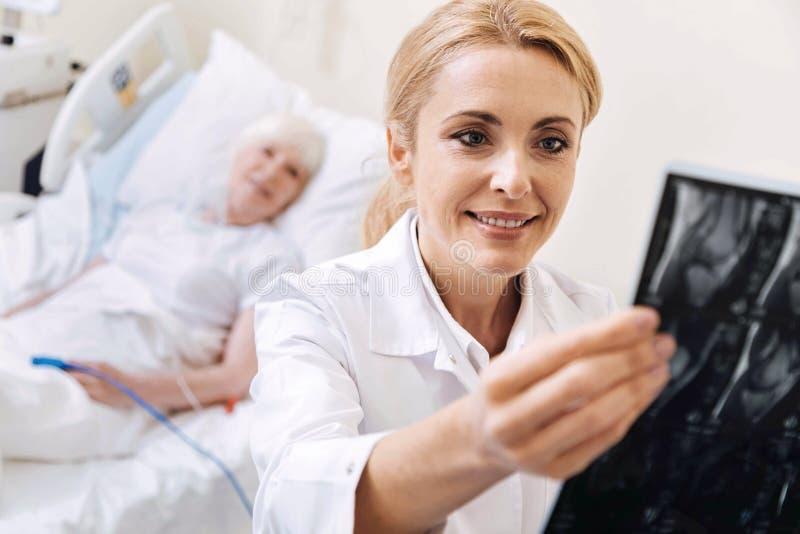 Docteur qualifié intelligent examinant le balayage de son patient plus âgé image libre de droits
