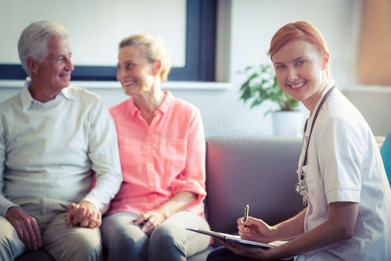 Docteur rédigeant le rapport médical des couples supérieurs image libre de droits