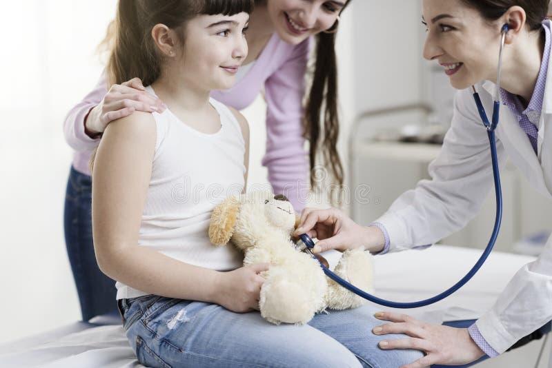 Docteur rendant visite à une fille mignonne et jouant avec elle image stock