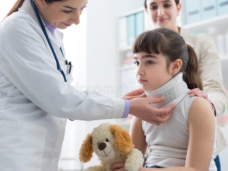 Docteur rendant visite à une jeune fille avec le collier cervical photographie stock libre de droits
