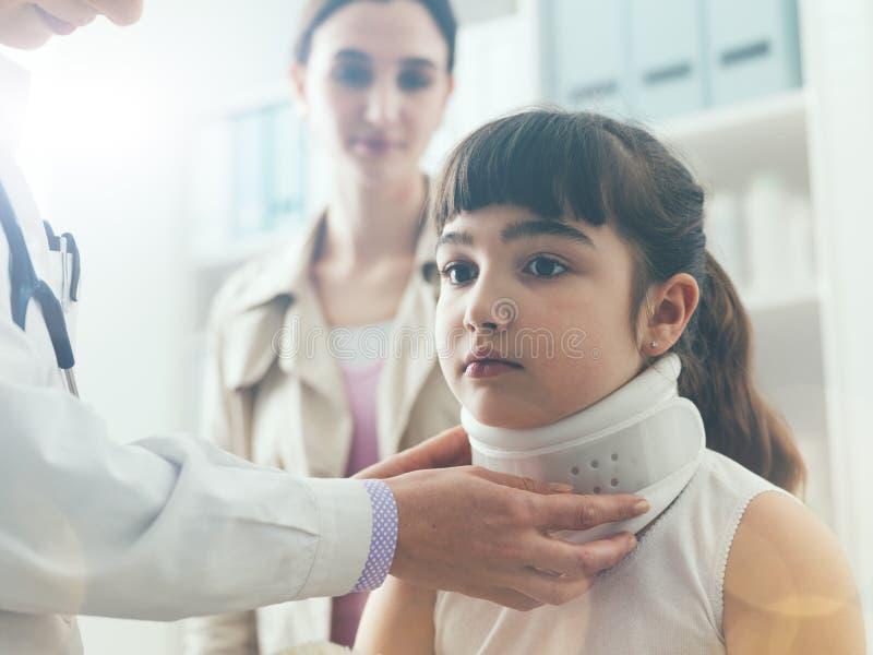 Docteur rendant visite à une jeune fille avec le collier cervical photographie stock