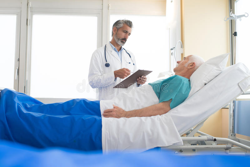 Docteur rendant visite au patient supérieur à l'hôpital photographie stock