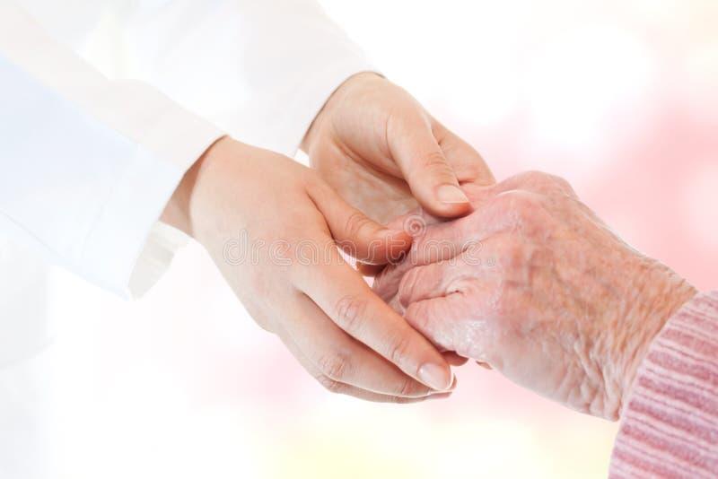 Docteur retenant la main de la dame aînée photos libres de droits