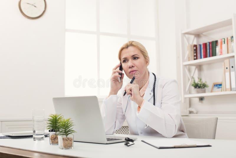 Docteur sérieux parlant au téléphone avec le patient images stock