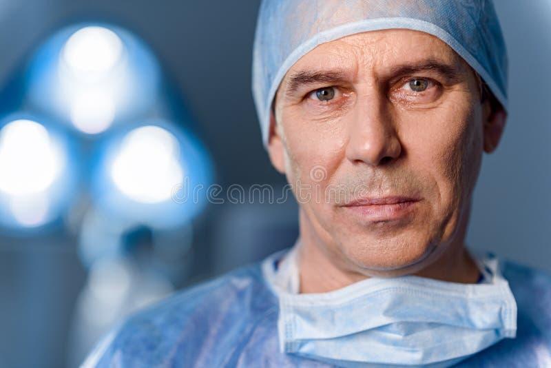 Docteur sérieux se tenant dans la salle d'opération photographie stock libre de droits