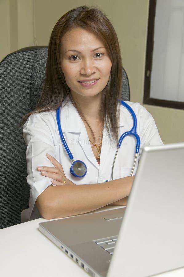Docteur s'asseyant à son bureau photographie stock libre de droits
