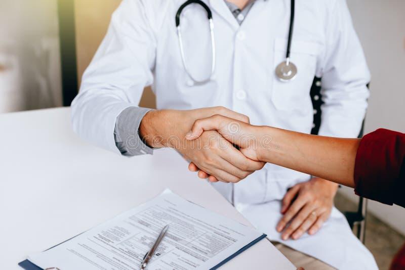 Docteur serrant la main au patient dans la clinique images stock