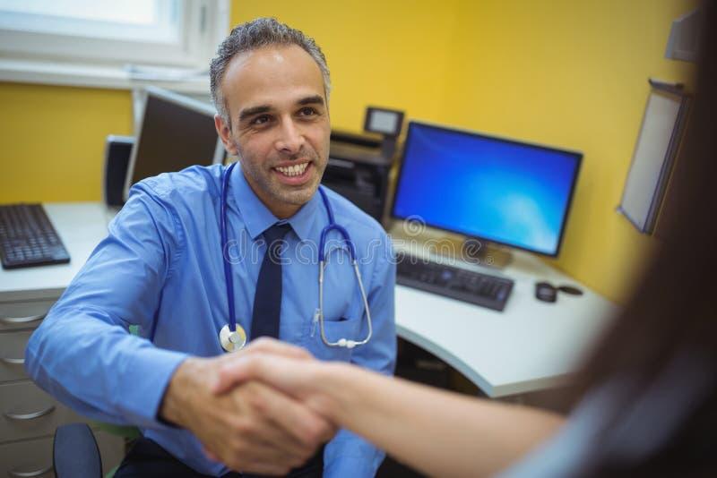 Docteur serrant la main avec le patient pendant la visite photographie stock