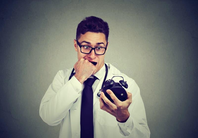 Docteur soucieux soumis à une contrainte, réveil se tenant professionnel de soins de santé fait pression sur par temps images libres de droits
