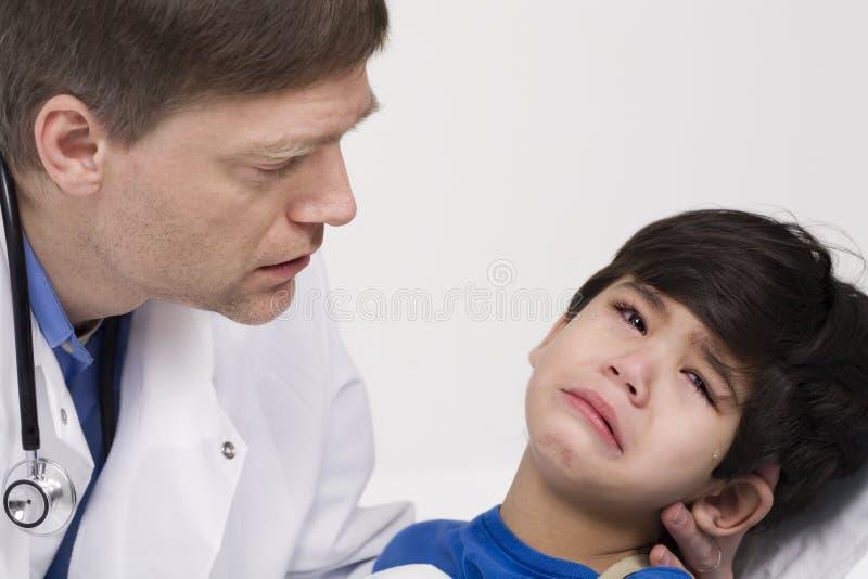 Docteur soulageant un petit garçon effrayé photo libre de droits